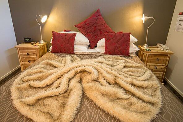 Queen Sized bed with fluffy rug at Lakefront Lodge