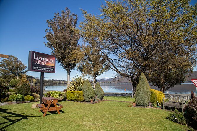 Signage at front of Lakefront Lodge with Lake Te Anau in the background