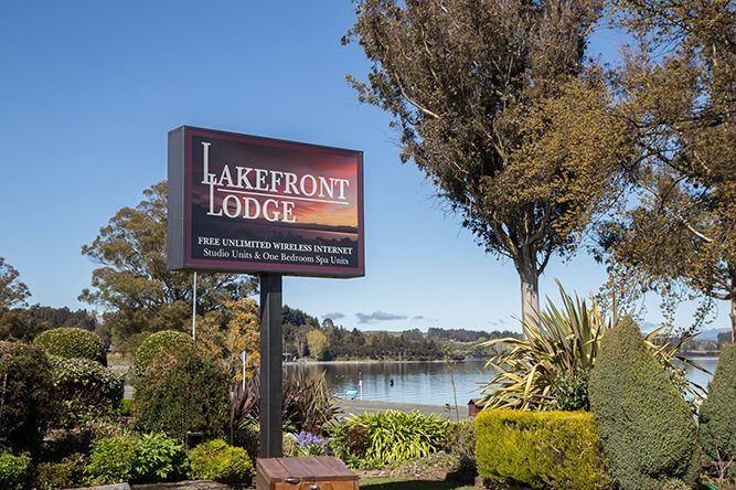 Close up of Lakefront Lodge sign with Lake Te Anau in the background