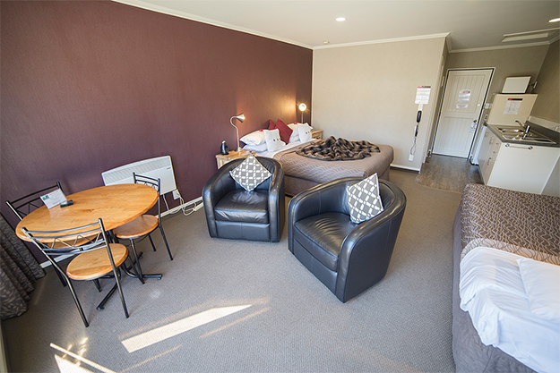 Interior of studio style accommodation showing the beds, seating area and kitchenette